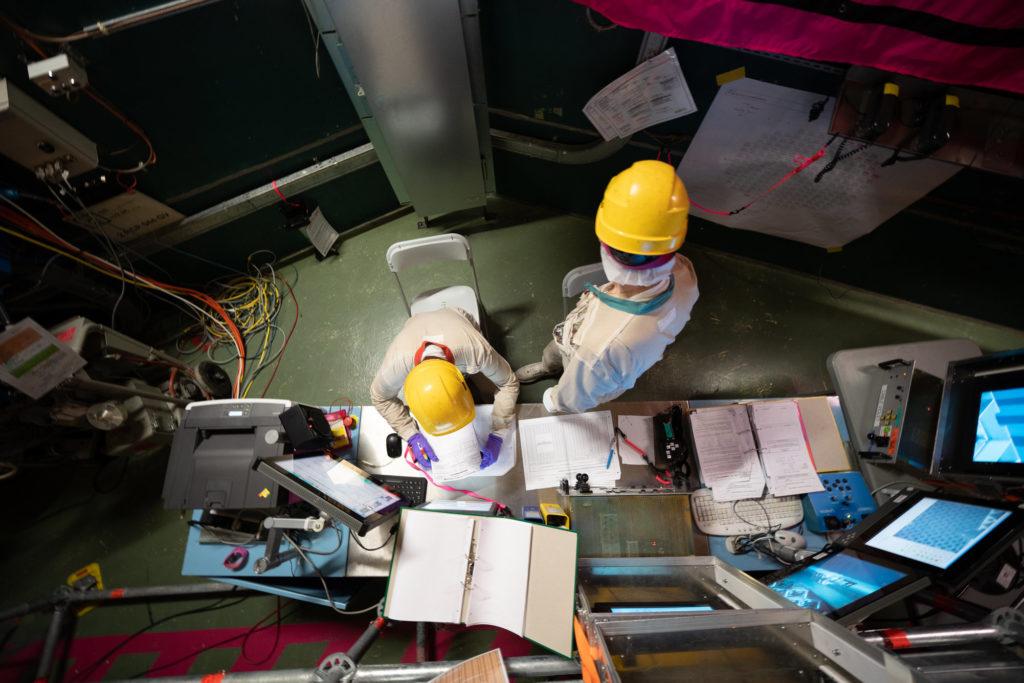 deux hommes en habits de travail commande un reacteur nucleaire